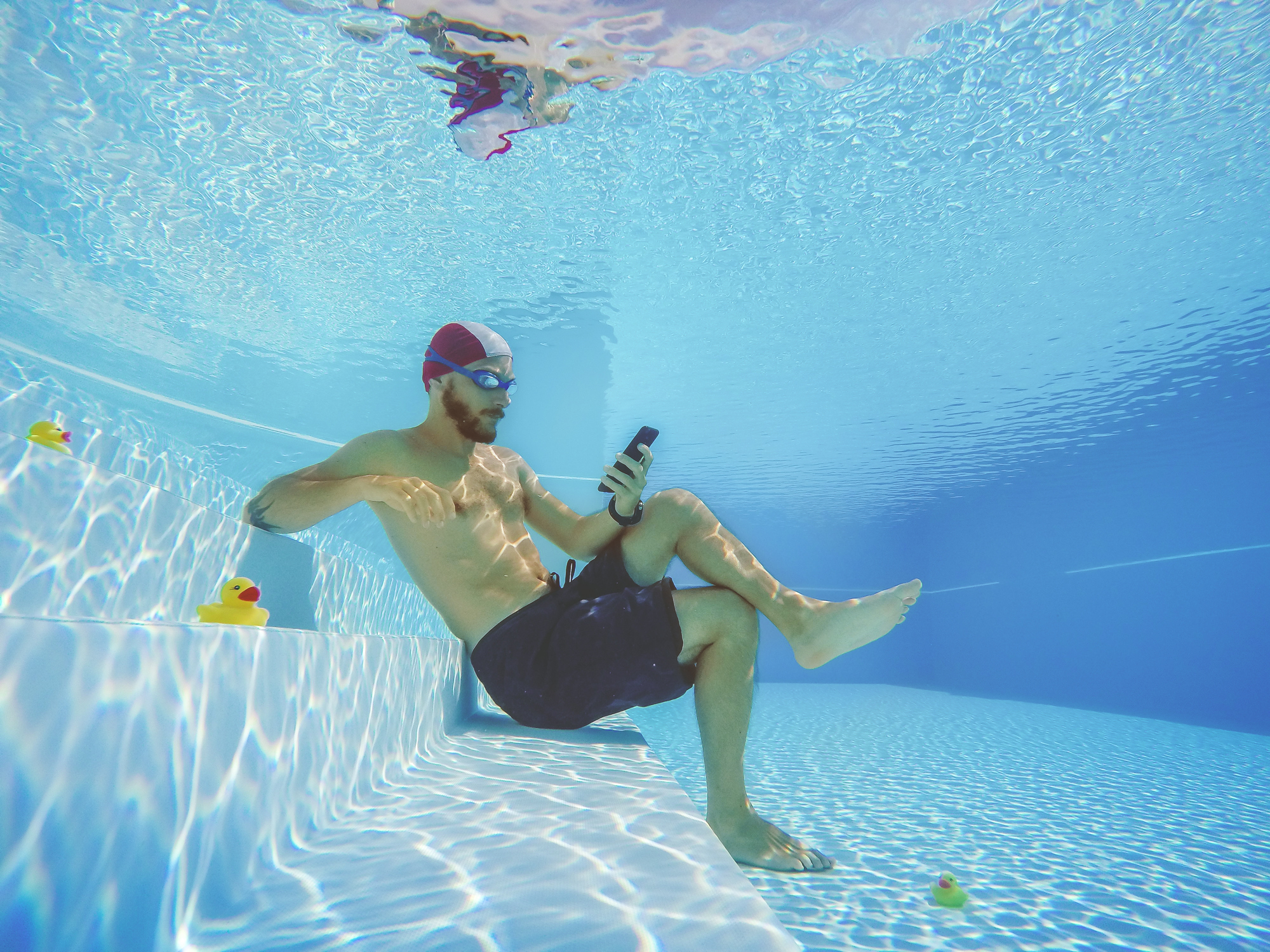 man underwater, social networking on the mobile phone.