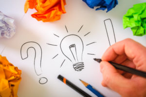 a hand holding a pen to paper beside a drawing of a question mark and a light bulb. Several crumpled up pieces of colored paper are also laid over the page.