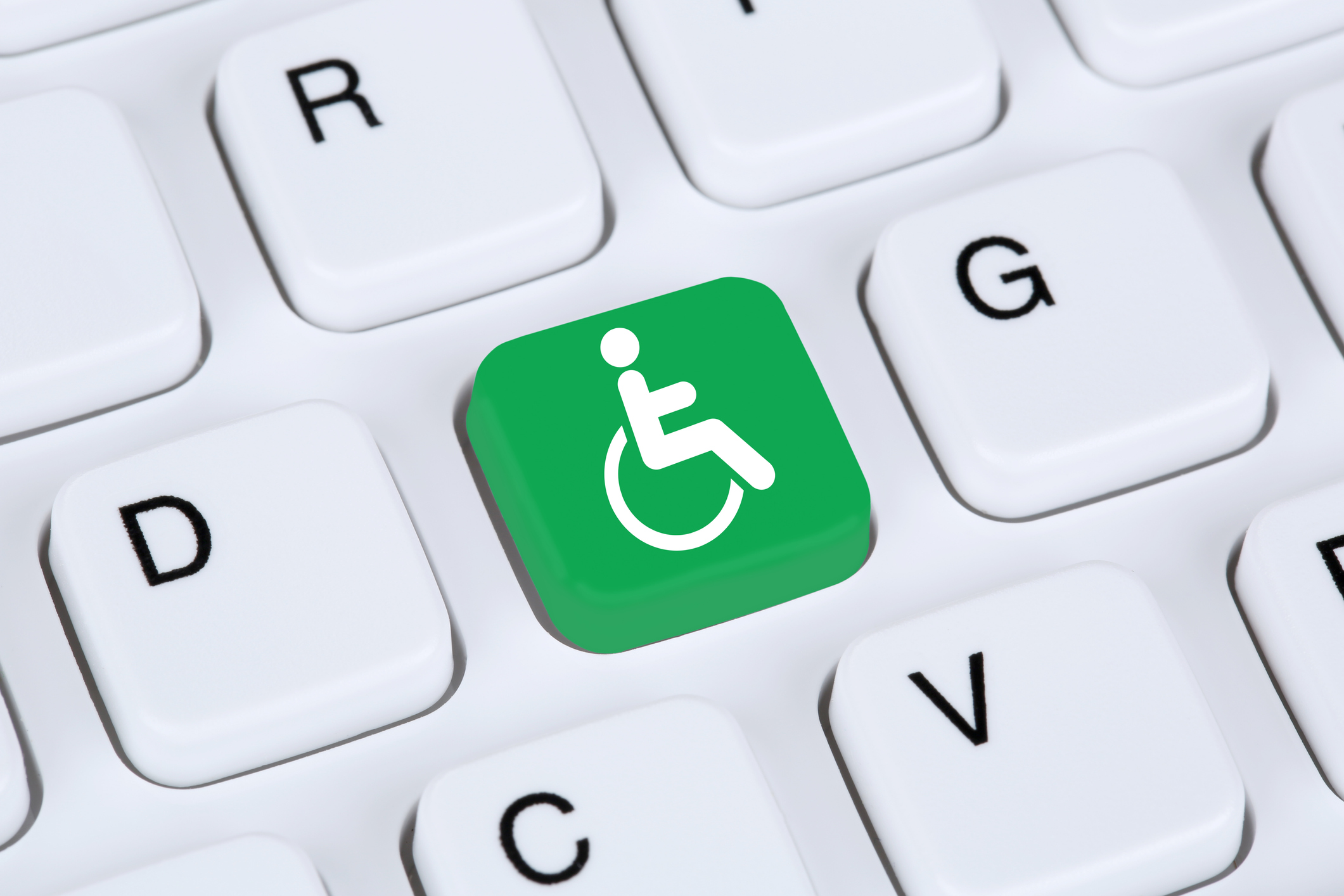 Keyboard with F key replaced by a white stick figure in a wheelchaire on a green background.