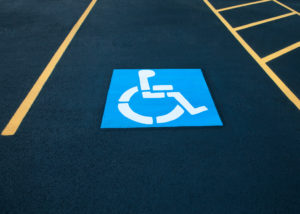 Disabled blue parking sign painted on dark asphalt with yellow lines