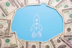 drawing of a rocket launching surrounded by money.